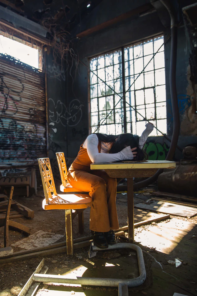 a girl sitting at a table in an abandoned building, looking forlorn with her head in her hands